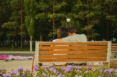 El amor, relaciones, pares, sensación, tranquilidad, banco, parque, flor, árbol, se relaja imagen de archivo