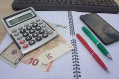 El análisis, la calculadora y la pluma de la tabla del mercado de acción indica la investigación y el análisis, con efectivo Foto de archivo libre de regalías