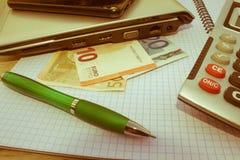 El análisis, la calculadora y la pluma de la tabla del mercado de acción indica la investigación y el análisis, con efectivo Imagen de archivo