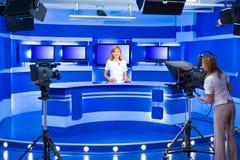 El anchorwoman y el teleoperador de la televisión trabajan en el estudio de la TV Foto de archivo libre de regalías