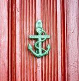 El ancla antigua formó el knokcer en una puerta roja del vintage Fotografía de archivo libre de regalías