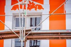 El andamio del pintor con la casa anaranjada en el fondo foto de archivo libre de regalías