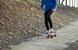 El andar en monopatín a lo largo de una trayectoria del cemento Foto de archivo