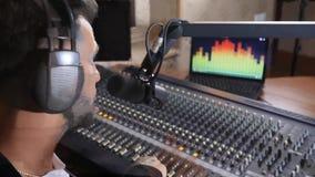 El anfitrión de radio agradable en auriculares habla en el micrófono y hace sano más ruidosamente en la consola de mezcla en estu almacen de metraje de vídeo