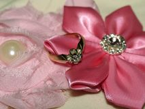 El anillo de diamante en las flores de satén de los pétalos Imágenes de archivo libres de regalías
