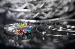 El anillo de plata con los diamantes coloreados y la otra joyería en un fondo negro imagen de archivo libre de regalías