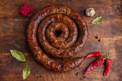 El anillo espiral de la salchicha cocido en un horno viejo está en un tablero de madera con pimienta y ajo fotos de archivo
