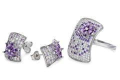 El anillo y los pares de plata tachonan los pendientes sobre un fondo blanco Imágenes de archivo libres de regalías