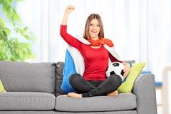 El animar femenino del fanático del fútbol asentado en el sofá en casa Foto de archivo libre de regalías