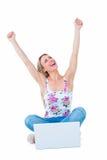 El animar rubio feliz con los brazos sube cerca de su ordenador portátil Fotografía de archivo