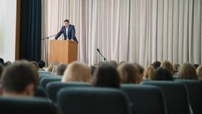 El anunciador de sexo masculino conduce un seminario en el pasillo almacen de video
