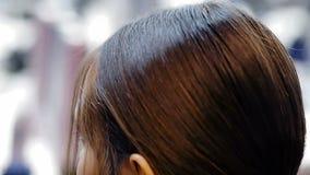 El aparador del pelo funciona un producto del cuidado del cabello como el estadio final para el primer modelo femenino en el entr almacen de video