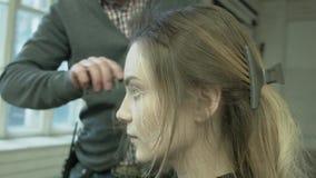 El aparador profesional del pelo utilizó un hairdryer Estilista de sexo masculino con un hairdryer La mujer joven que le conseguí metrajes