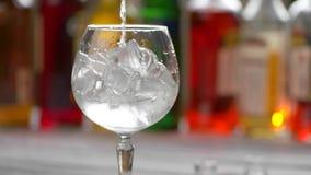 El aparejo vierte la bebida en el vidrio metrajes