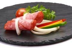 El aperitivo sabroso del salami picante fino cortado fum? el colorfull del whith de la salchicha vegetabless en un tablero r?stic fotografía de archivo