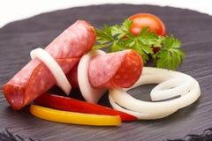 El aperitivo sabroso del salami picante fino cortado fum? el colorfull del whith de la salchicha vegetabless en un tablero r?stic fotografía de archivo libre de regalías