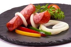 El aperitivo sabroso del salami picante fino cortado fum? el colorfull del whith de la salchicha vegetabless en un tablero r?stic fotos de archivo