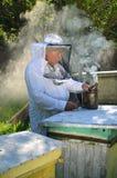 El apiarist mayor experimentado está fijando un fuego en un fumador de la abeja Imagen de archivo
