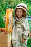 El apicultor del muchacho sostiene en sus manos un panal con la miel fresca Concepto de la apicultura Fotografía de archivo