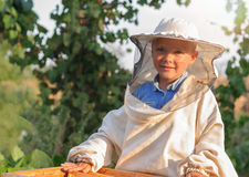 El apicultor del niño pequeño trabaja en un colmenar en la colmena Imágenes de archivo libres de regalías