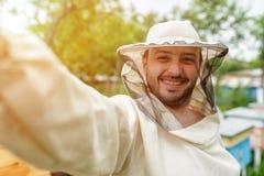 El apicultor se quita en la cámara de la acción del colmenar Blog video Foto de archivo libre de regalías