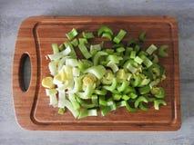 El apio verde fresco proviene en el primer de madera de la tabla de cortar foto de archivo libre de regalías