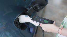 El app en el teléfono conecta con el coche eléctrico y exhibe la carga auto de la batería metrajes