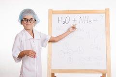 El aprendiz en clase de química muestra en las fórmulas en una pizarra Foto de archivo