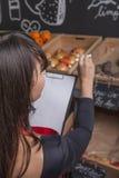 El aprendiz femenino cuenta las frutas mientras que el inventario Foto de archivo libre de regalías