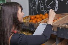 El aprendiz femenino cuenta las frutas mientras que el inventario Fotos de archivo