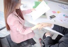 El apretón de manos entre el hombre de negocios y las mujeres jovenes confía el contrato de sociedad del negocio imagen de archivo