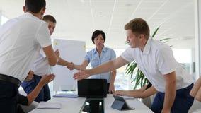 El apretón de manos y aplaude de socios comerciales acertados en la tabla grande en la sala de reunión almacen de metraje de vídeo