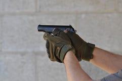 El apuntar y el tirar 45 arma de la mano del calibre 1911 con los guantes imagen de archivo libre de regalías