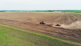 El arado del tractor monta en un campo grande, visión superior almacen de video
