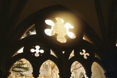 El arck gótico adornó la ventana a una yarda de la iglesia con una catedral a Foto de archivo libre de regalías