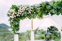 El arco blanco adornado con las flores, florales para el lugar de la boda Imagen de archivo