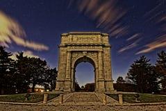 El arco conmemorativo nacional en la noche foto de archivo