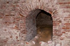El arco constructivo abandonado viejo de la pared de ladrillo resistió, aventura peligrosa de la catacumba abandonada de la forta Fotos de archivo libres de regalías