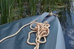 El arco del barco inflable con la cuerda a bordo se amarra en el río imagenes de archivo