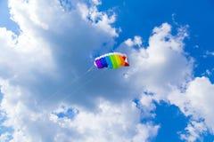 El arco iris coloreó la cometa del niño en el cielo azul con las nubes Foto de archivo libre de regalías
