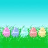 El arco iris de Pascua eggs en hierba brillante en un fondo del cielo azul Fotos de archivo libres de regalías