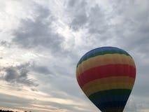 El arco iris redondo brillante multicolor grande coloreó el globo rayado rayado del vuelo con una cesta contra el cielo por la ta foto de archivo