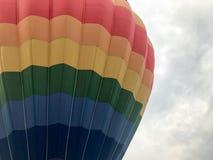 El arco iris redondo brillante multicolor grande coloreó el globo rayado rayado del vuelo con una cesta contra el cielo por la ta imagen de archivo libre de regalías