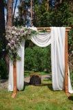 El arco para la ceremonia de boda del paño beige y de madera abre una sesión el parque del pino Foto de archivo