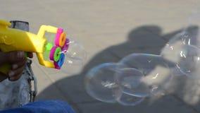 El arma colorido plástico del fabricante de burbuja en mano adolescente joven en área al aire libre almacen de metraje de vídeo