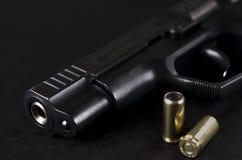 El arma negro miente en un fondo negro al lado de las balas fotos de archivo libres de regalías