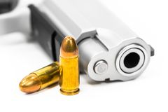 El arma y las balas pusieron el piso blanco fotografía de archivo libre de regalías