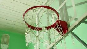 El aro de baloncesto y una cartelera en el gimnasio de la escuela se divierten almacen de video