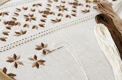 El aro de madera con el modelo del bordado del color marrón y beige en lona, en la tabla de madera Estilo rústico Foco selectivo fotos de archivo libres de regalías
