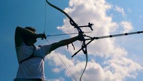 El arquero de sexo masculino está en el medio de apuntar proceso Tiroteo con un arco y las flechas almacen de metraje de vídeo